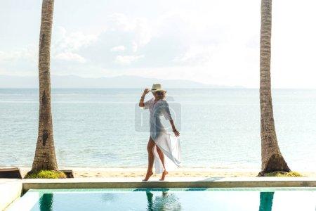 Photo pour Mince fille debout entre piscine et océan à la station tropicale - image libre de droit