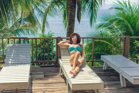 Photo for Attractive girl lying in bikini and hat on lounge chair at tropical resort - Royalty Free Image