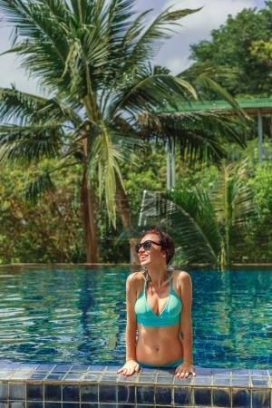 Foto de Sonrisa a hermosa chica en bikini, apoyándose junto a la piscina - Imagen libre de derechos