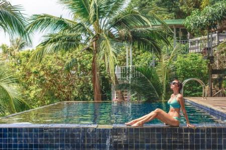 Photo pour Belle fille en bikini assis sur le bord de la piscine et levant les yeux - image libre de droit