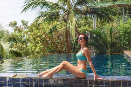 Photo pour Belle fille en bikini assis sur le bord de la piscine et regardant loin - image libre de droit