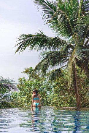 Photo pour Vue arrière de la fille séduisante en bikini dans la piscine à la station tropicale - image libre de droit
