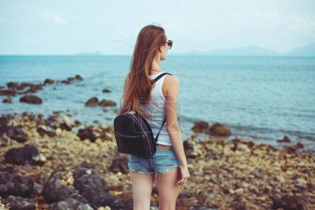 Photo for Back view of young woman in sunglasses with backpack looking at ocean - Royalty Free Image