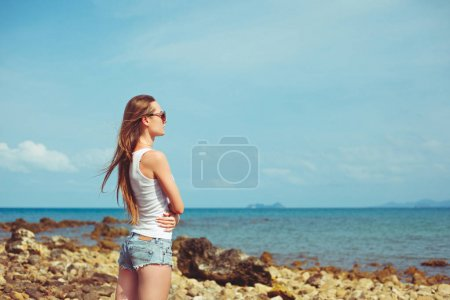 Photo for Side view of young woman in sunglasses looking at ocean - Royalty Free Image