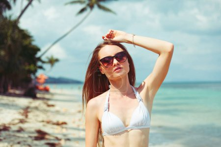 Photo for Portrait of young woman in bikini and sunglasses on coastline near ocean - Royalty Free Image