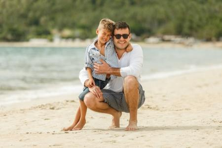 Photo for Happy handsome father and son embracing on tropical beach - Royalty Free Image
