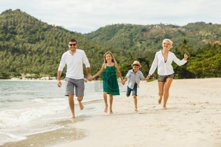 Photo pour Jeune famille heureuse courue par la plage sur l'île tropicale - image libre de droit