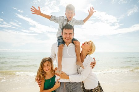 Photo for Beautiful family on vacation standing together in front of ocean - Royalty Free Image
