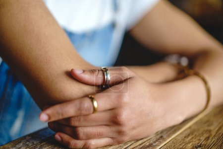 Photo for Male hands with rings and bracelet leaning on table - Royalty Free Image
