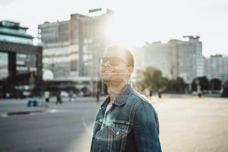 Photo pour Souriant le jeune homme à lunettes de soleil sur la rue de la ville - image libre de droit