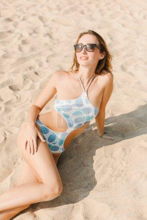 Photo pour Belle fille mince dans des lunettes de soleil se détendre sur la plage de sable - image libre de droit