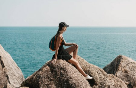 Photo for Girl sitting on rocks and looking at the sea - Royalty Free Image
