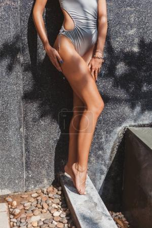 Photo for Cropped shot of seductive woman in grey swimsuit with tanned legs - Royalty Free Image