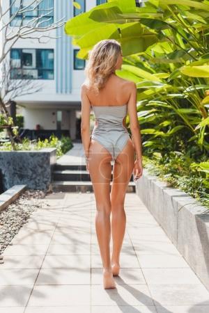 Photo pour Vue arrière de belle jeune femme en maillot de bain gris au resort - image libre de droit