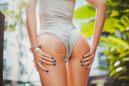 Photo for Cropped shot of seductive woman in grey swimsuit with hands on buttocks - Royalty Free Image