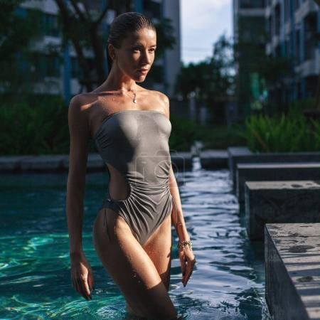 Photo for Seductive young woman in wet swimsuit standing in pool - Royalty Free Image