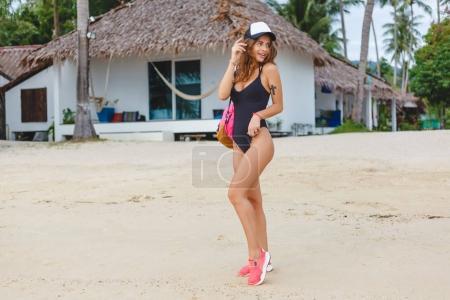 Foto de Hermosa chica posando en traje de baño negro y gorra con mochila en la playa - Imagen libre de derechos