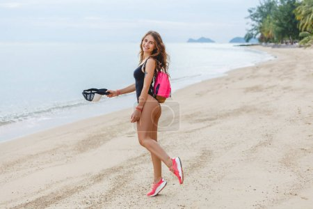 Photo for Beautiful slim girl posing with cap and backpack on sandy beach near sea - Royalty Free Image