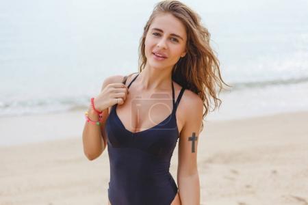 Photo pour Attrayant mince fille en maillot de bain noir posant sur la plage de sable près de la mer - image libre de droit