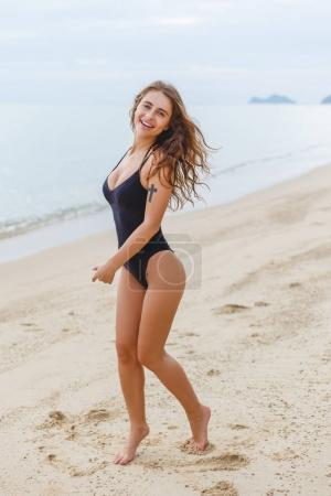 Photo for Beautiful slim girl in swimsuit posing on sandy beach - Royalty Free Image