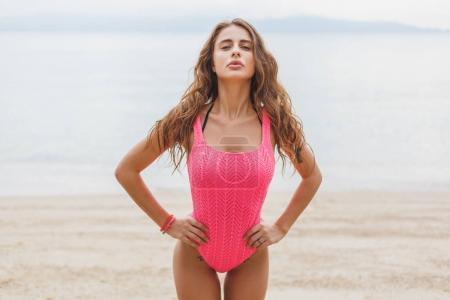 Photo pour Jolie fille posant en maillot de bain rose sur la plage près de la mer - image libre de droit