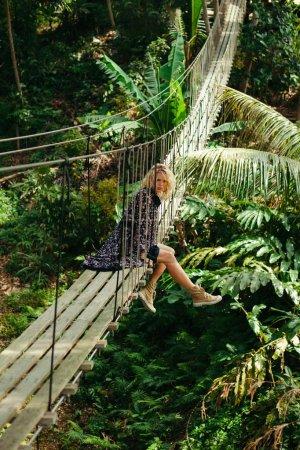 Foto de Atractiva mujer sentada en el puente colgante de madera en selva - Imagen libre de derechos