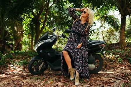 Foto de Mujer atractiva en gafas de sol sentado en la moto negra en selva - Imagen libre de derechos