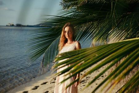 Photo pour Attrayant femme debout entre les feuilles de palmier sur la plage de l'océan - image libre de droit