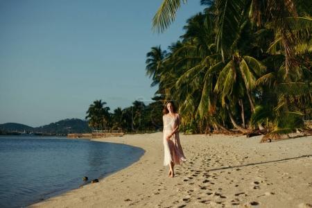 Photo pour Belle femme marchant en robe sur la plage de l'océan - image libre de droit