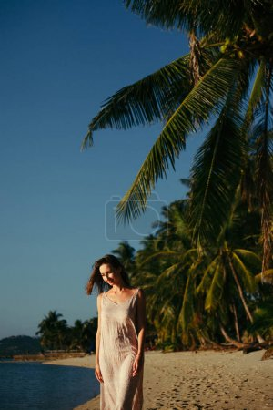 smiling attractive woman standing on ocean beach at tropical resort
