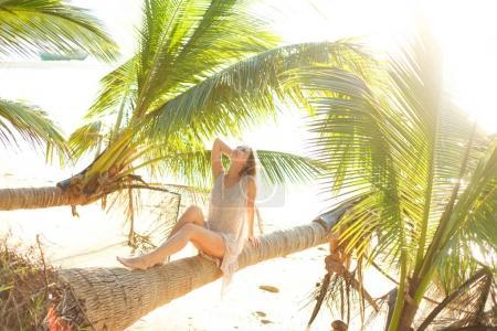 Photo pour Femme séduisante posant sur un palmier tombé sur la plage de l'océan - image libre de droit