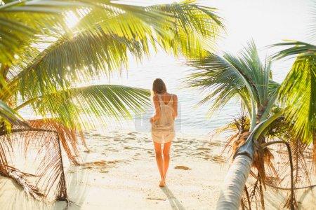 Photo pour Vue arrière de la femme debout entre les palmiers sur la plage de la mer - image libre de droit