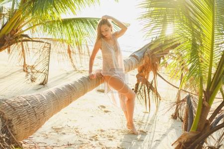 Photo pour Séduisante femme posant près de palmier tombé sur la plage de l'océan - image libre de droit