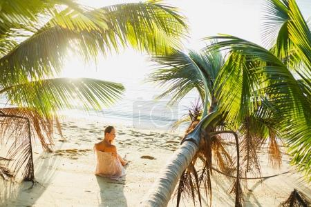 attractive woman sitting between palm trees on ocean beach