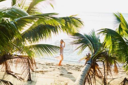 Photo pour Belle femme posant entre les palmiers sur la plage de l'océan - image libre de droit