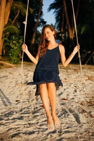 Photo pour Femme heureuse avec balançoire entre palmiers, regardant la caméra sur la plage - image libre de droit
