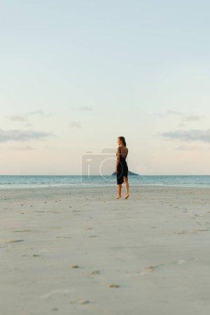 Photo pour Vue arrière du femme qui marche sur la plage de sable de robe pendant le coucher du soleil - image libre de droit