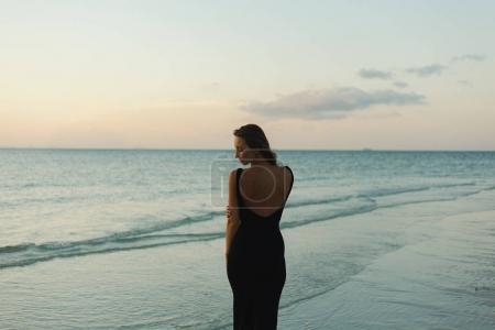 Photo pour Attrayant femme debout en robe sur la plage de l'océan pendant le coucher du soleil - image libre de droit