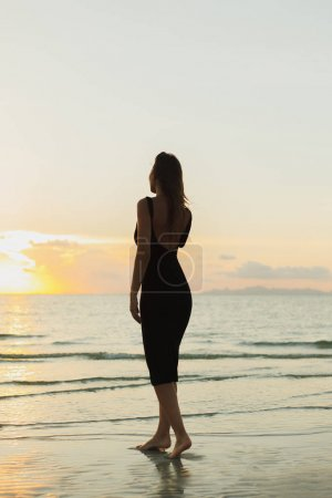 back view of attractive woman standing barefoot on ocean sandy beach during sunset