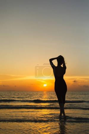 Photo pour Vue arrière de la silhouette de la femme posant dans l'océan au coucher du soleil - image libre de droit