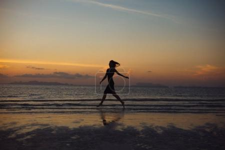 Photo for Silhouette of woman running on ocean beach during sunset - Royalty Free Image