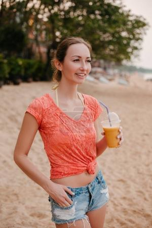 smiling attractive girl standing with cocktail on sandy beach and looking away
