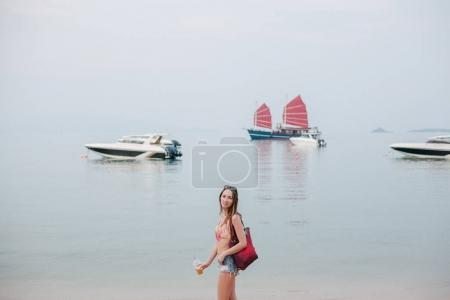 attractive girl with cocktail standing on ocean beach with yachts on background