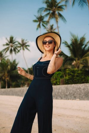Photo for Smiling attractive woman touching hat on sandy ocean beach - Royalty Free Image