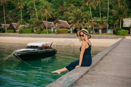 Photo pour Vue latérale de belle femme en chapeau et robe assis sur la jetée près de l'océan - image libre de droit
