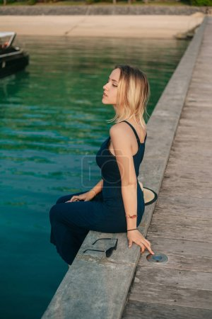 side view of sensual attractive girl sitting in dress on pier