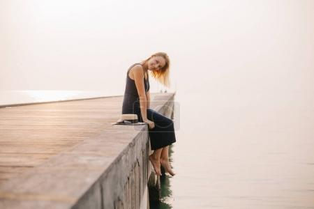 Photo for Side view of smiling attractive girl sitting in dress on pier near ocean - Royalty Free Image