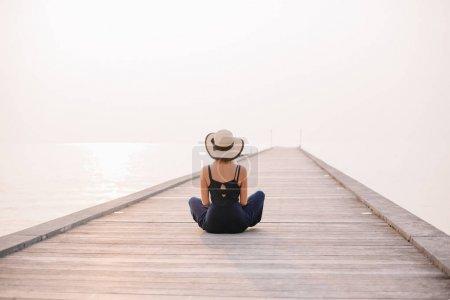 Photo pour Vue arrière de la femme en chapeau assis sur la jetée près de l'océan - image libre de droit