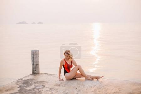 Photo pour Belle fille assise sur la jetée en maillot de bain près de l'océan - image libre de droit