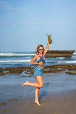 Foto de Mujer joven atractiva con naranja y piña en la playa - Imagen libre de derechos